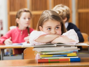 Girl (4-7) sitting desk, leaning on stack of books --- Image by © Westend61/Corbis